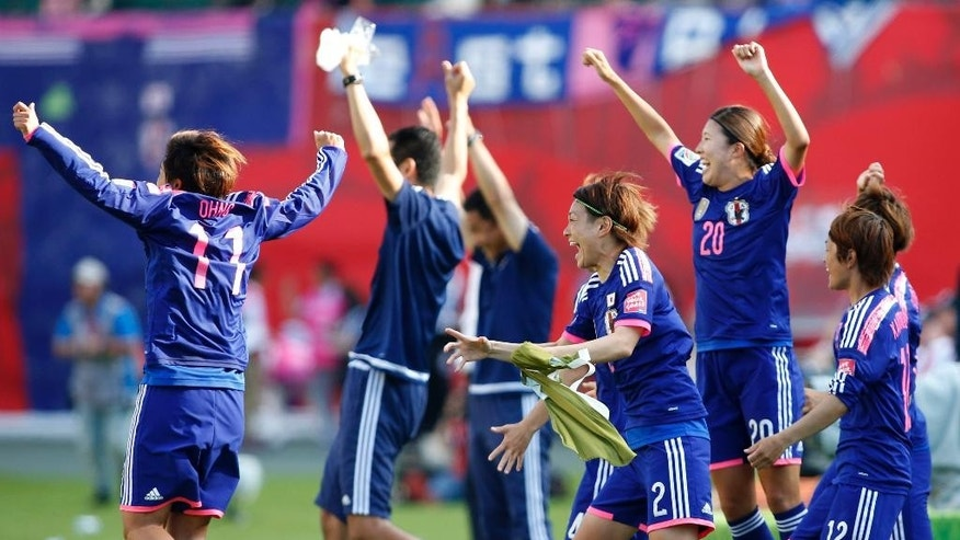 Japan players race onto the field to celebrate a 2-1 win over England in a semifinal in the FIFA Women's World Cup soccer tournament, Wednesday, July 1, 2015, in Edmonton, Alberta, Canada. (Jeff McIntosh/The Canadian Press via AP)