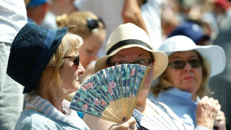 A spectators fans herself on Centre Court as they watch the singles match between Novak Djokovic of Serbia and Jarkko Nieminen of Finland, at the All England Lawn Tennis Championships in Wimbledon, London, Wednesday July 1, 2015. (AP Photo/Alastair Grant)