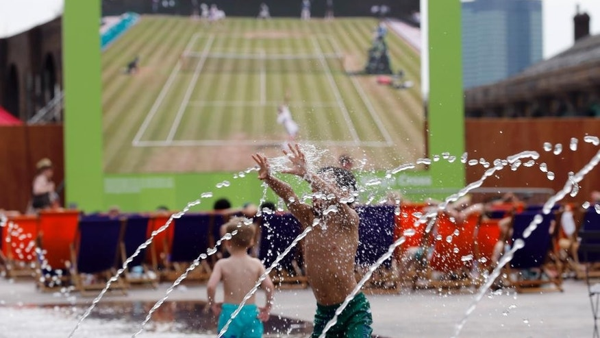 Six-year-old Harvey enjoys playing with water as the Wimbledon Tennis Championships are seen on a huge screen in London, Wednesday, July 1, 2015.  Britain is preparing itself for the hottest day of the year Wednesday, with temperatures possibly rising to 34C (93F).(AP Photo/Frank Augstein)