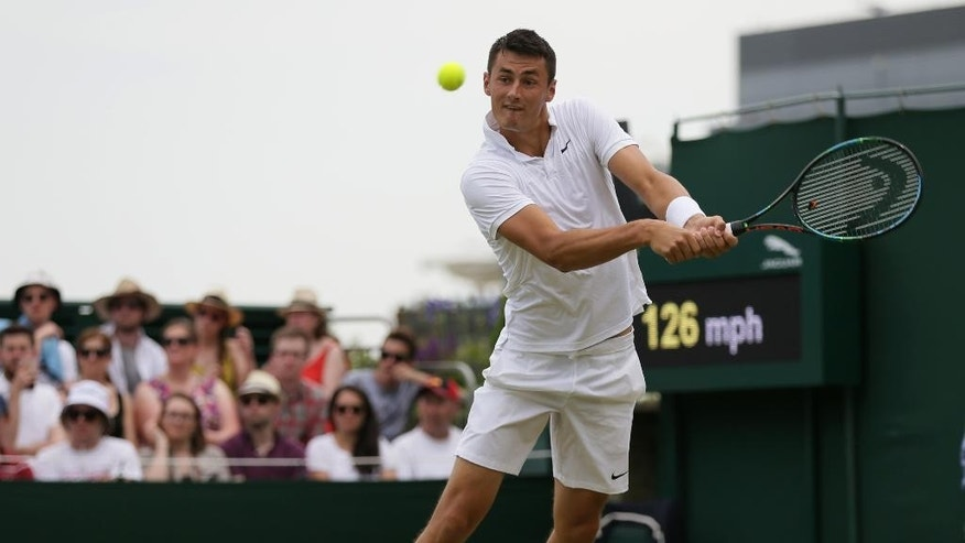 Bernard Tomic of Australia returns a shot to Pierre-Hugues Herbert of France during the men's singles match against at the All England Lawn Tennis Championships in Wimbledon, London, Wednesday July 1, 2015. (AP Photo/Tim Ireland)