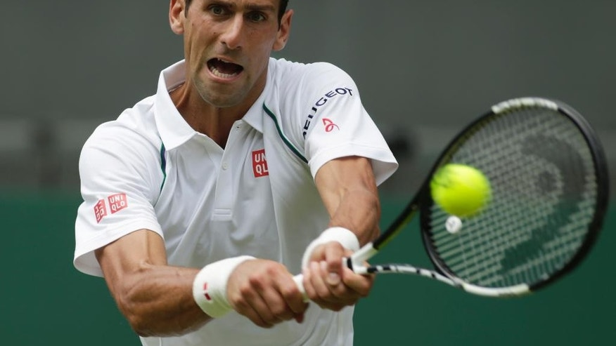 Novak Djokovic of Serbia plays a return to Jarkko Nieminen of Finland, during their singles match at the All England Lawn Tennis Championships in Wimbledon, London, Wednesday July 1, 2015. (AP Photo/Alastair Grant)