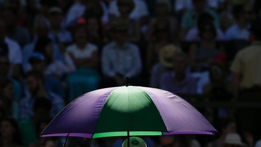 Sun rays fall on an umbrella during a break in the singles first round match between  Andy Murray of Britain and Mikhail Kukushkin of Kazakhstan at the All England Lawn Tennis Championships in Wimbledon, London, Tuesday June 30, 2015. (AP Photo/Tim Ireland)