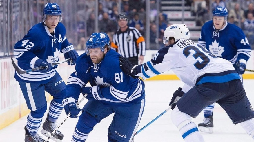 FILE - In this Feb. 21, 2015, file photo, Toronto Maple Leafs' Phil Kessel, second from left, skates past Winnipeg Jets' Toby Enstrom, second from right, and Maple Leafs teammates Tyler Bozak, left, and Morgan Rielly during overtime NHL hockey action in Toronto. The Maple Leafs sent 27-year-old Kessel to the Pittsburgh Penguins on Wednesday, July 1, 2015, in a blockbuster deal that gives the Penguins a needed boost in its top six and gives the Maple Leafs some flexibility as they begin to retool under new coach Mike Babcock. (Darren Calabrese/The Canadian Press via AP, File)