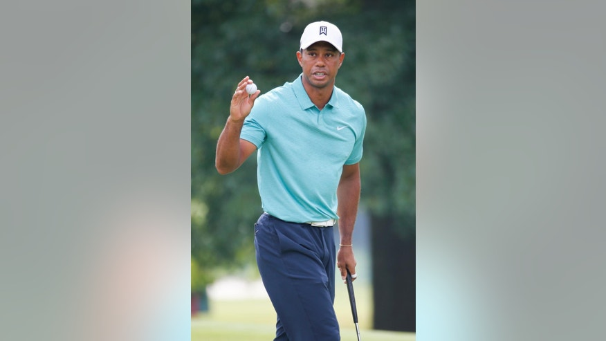 Tiger Woods tips his ball to the crowd after a birdie on the 16th hole during the first round of the Greenbrier Classic golf tournament at the Greenbrier Resort  in White Sulphur Springs, W.Va., Thursday, July 2, 2015.  (AP Photo/Steve Helber)