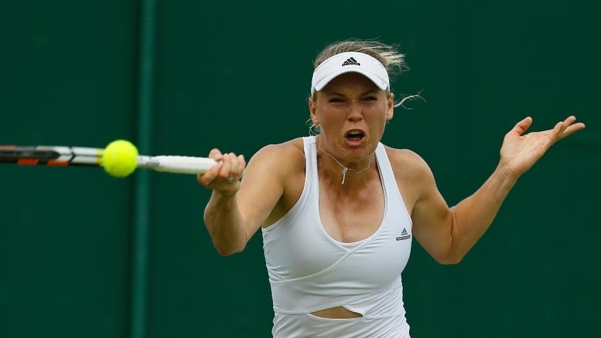 Caroline Wozniacki of Denmark makes a return to Denisa Allertova of the Czech Republic, during their singles match at the All England Lawn Tennis Championships in Wimbledon, London, Thursday July 2, 2015. (AP Photo/Kirsty Wigglesworth)