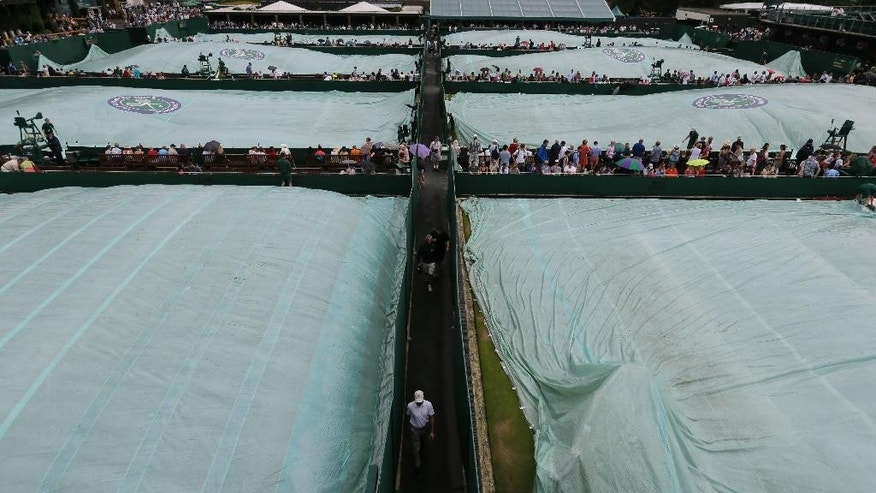 Rain covers are seen on the courts, on the fourth day of play, at the All England Lawn Tennis Championships in Wimbledon, London, Thursday July 2, 2015. (AP Photo/Tim Ireland)
