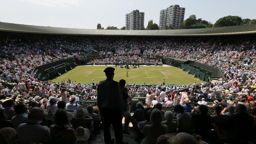 Spectators on No. 1 Court watch the match between Milos Raonic of Canada and Tommy Haas of Germany at the All England Lawn Tennis Championships in Wimbledon, London, Wednesday July 1, 2015. (AP Photo/Tim Ireland)