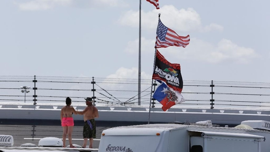 Race fans with an American flag and various other flags watch cars on the track from the top of a motorhome during a NASCAR Sprint Cup practice session at Daytona International Speedway, Friday, July 3, 2015, in Daytona Beach, Fla. (AP Photo/John Raoux)
