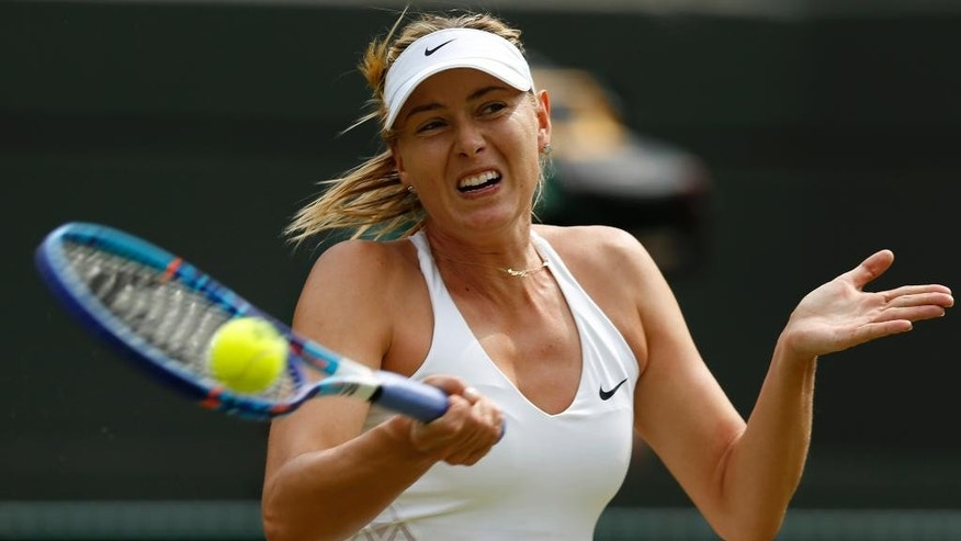 Maria Sharapova of Russia makes a return to Irina-Camelia Begu of Romania, during their singles match at the All England Lawn Tennis Championships in Wimbledon, London, Friday July 3, 2015. (AP Photo/Pavel Golovkin)