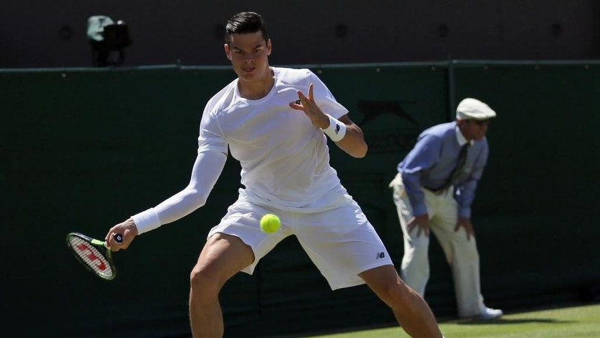 Milos Raonic of Canada returns a ball to Nick Kyrgios of Australia during their singles match at the All England Lawn Tennis Championships in Wimbledon, London, Friday July 3, 2015. (AP Photo/Tim Ireland)