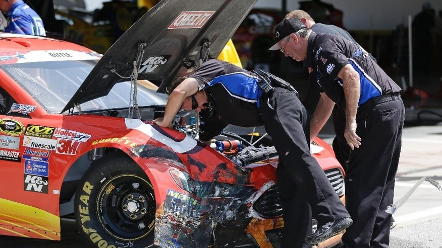 Crew members for Greg Biffle repair damage to his car after he was involved in a wreck during a NASCAR Sprint Cup practice session at Daytona International Speedway, Friday, July 3, 2015, in Daytona Beach, Fla. (AP Photo/John Raoux)