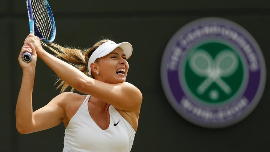 Maria Sharapova of Russiareturns a ball to   Irina-Camelia Begu of Romania during their singles match at the All England Lawn Tennis Championships in Wimbledon, London, Friday July 3, 2015. (AP Photo/Pavel Golovkin)