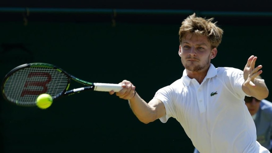 David Goffin of Belgium returns a ball to  Marcos Baghdatis of Cyprus, during their singles match at the All England Lawn Tennis Championships in Wimbledon, London, Friday July 3, 2015. (AP Photo/Alastair Grant)