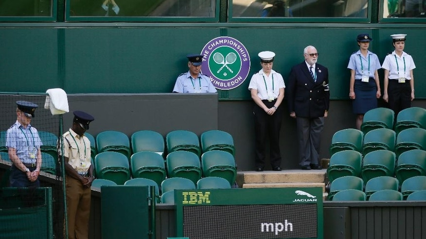 People observe the minute silence for the victims of the shooting in Tunisia last week, at the All England Lawn Tennis Championships in Wimbledon, London, Friday July 3, 2015. Fans and staff at Wimbledon observed a minute's silence for the victims of last Friday's attack in Tunisia, in which 30 Britons were killed in a shooting rampage at a beach resort in Sousse.  The start of play at Wimbledon was delayed so the tournament could join in the national minute's silence. (AP Photo/Kirsty Wigglesworth)