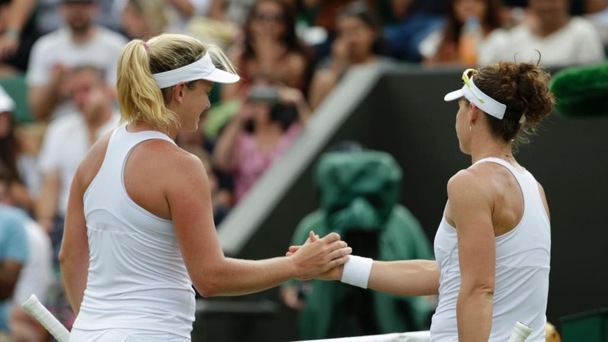 Coco Vandeweghe of the United States, left,  shakes hands at the net with Samantha Stosur of Australia, after their singles match, at the All England Lawn Tennis Championships in Wimbledon, London, Friday July 3, 2015. Vandeweghe won 6-2, 6-0. (AP Photo/Alastair Grant)