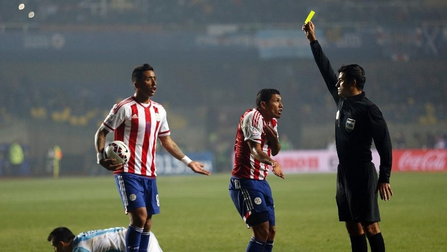 FILE - In this  June 30, 2015, file photo, referee Sandro Ricci, from Brazil, shows a yellow card to Paraguay's Richard Ortiz after he fouled Argentina's Sergio Aguero, right, during a Copa America semifinal soccer match at the Ester Roa Rebolledo Stadium in Concepcion, Chile. South American players are known for their vivid complaints and have long enjoyed more leeway when interacting with referees, especially compared to leagues in Europe, and now Brazil wants to put an end to that. (AP Photo/Silvia Izquierdo,File)