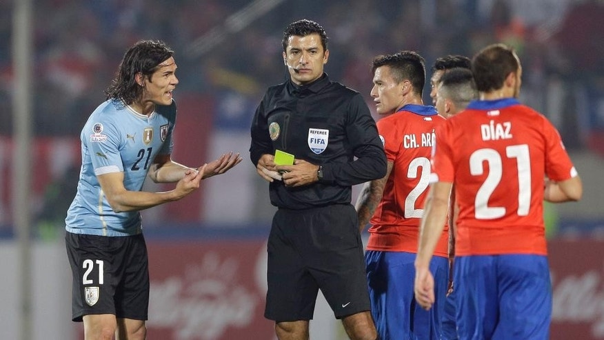 FILE - In this  June 24, 2015, file photo, Uruguay's Edinson Cavani  protests to referee Sandro Ricci, from Brazil, as he is being sent off with a red card after two yellow cards during a Copa America quarterfinal soccer match against Chile at the National Stadium in Santiago, Chile. Although some might think that in this case Cavani's complaint was justified, most agree that South American players are known for their vivid complaints and have long enjoyed more leeway when interacting with referees, especially compared to leagues in Europe, and now Brazil wants to put an end to that. (AP Photo/Jorge Saenz, File)
