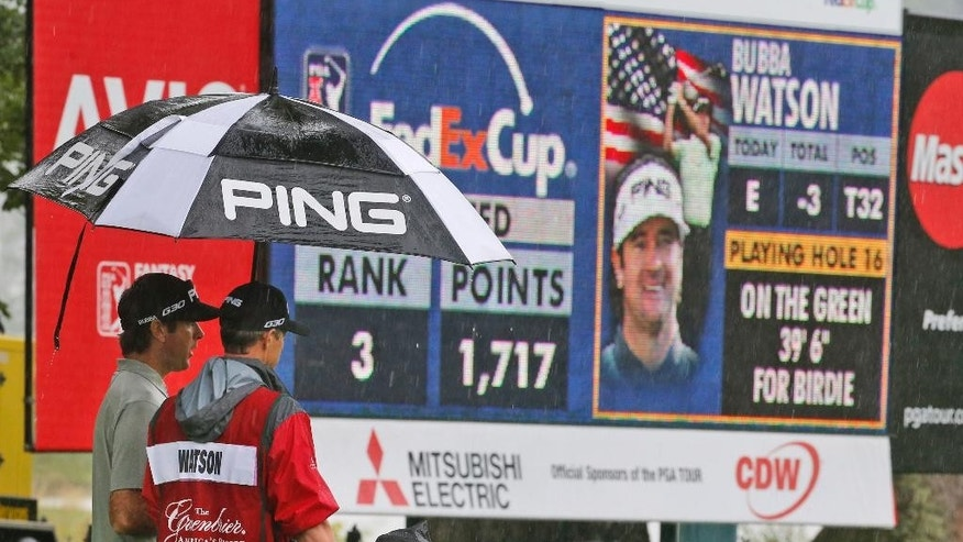 Bubba Watson, left, waits out a rain delay with his caddy  during the second round of the Greenbrier Classic golf tournament at the Greenbrier Resort  in White Sulphur Springs, W.Va., Friday, July 3, 2015. Rain caused delays in play.  (AP Photo/Steve Helber)