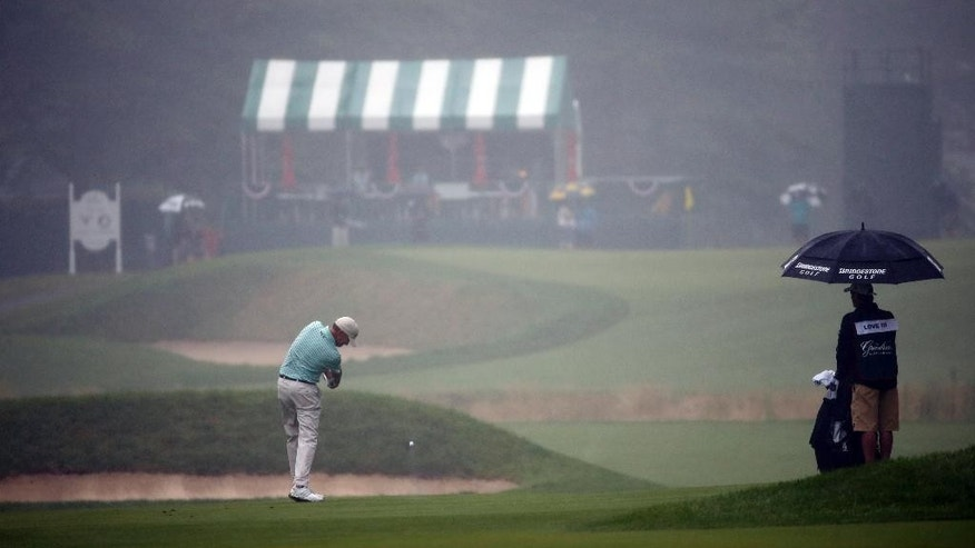 Davis Love III hits his second shot to a fog and rain shrouded 12th green during the second round of the Greenbrier Classic golf tournament at the Greenbrier Resort  in White Sulphur Springs, W.Va., Friday, July 3, 2015. Rain caused delays in play.  (AP Photo/Steve Helber)