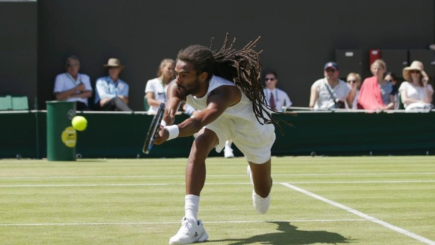 Dustin Brown of Germany returns the ball during his singles tennis match against Viktor Troicki of Serbia at the All England Lawn Tennis Championships in Wimbledon, London, Saturday July 4, 2015. (AP Photo/Pavel Golovkin)