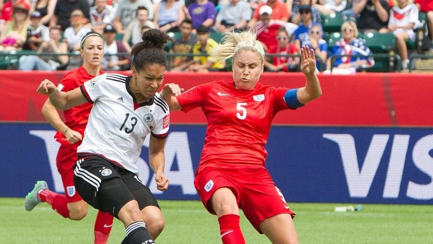 England's Steph Houghton (5) and Germany's Celia Sasic vie for the ball during first-half action of a FIFA Women's World Cup soccer game in Edmonton, Alberta, Canada, on Saturday, July 4, 2015. (Jason Franson/The Canadian Press via AP) MANDATORY CREDIT