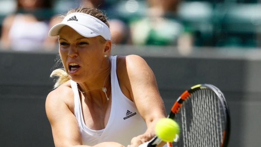 Caroline Wozniacki of Denmark returns a ball to Camila Giorgi of Italy during their singles match at the All England Lawn Tennis Championships in Wimbledon, London, Saturday July 4, 2015. (AP Photo/Kirsty Wigglesworth)