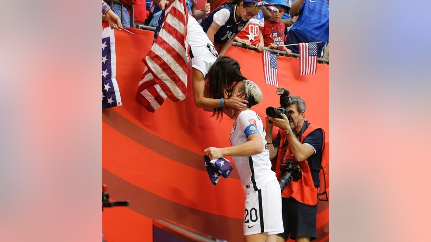 United States' Abby Wambach (20) gets a kiss from her wife, Sarah Huffman, after the U.S. beat Japan 5-2 in the FIFA Women's World Cup soccer championship in Vancouver, British Columbia, Canada, Sunday, July 5, 2015. (AP Photo/Elaine Thompson)