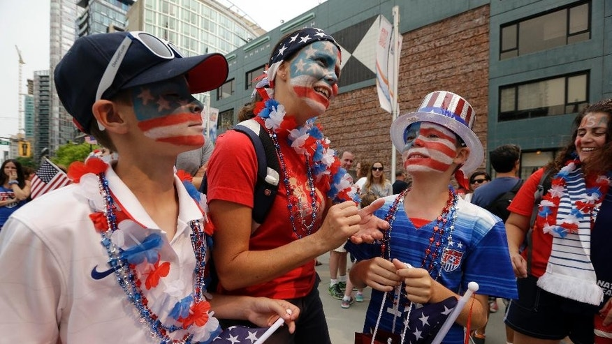 Stephanie Saylors, center, stands with her twin 11-year-old sons Lucas, left, and Aidan outside BC Place stadium before the FIFA Women's World Cup soccer championship between the United States and Japan in Vancouver, British Columbia, Canada, Sunday, July 5, 2015. (AP Photo/Elaine Thompson)