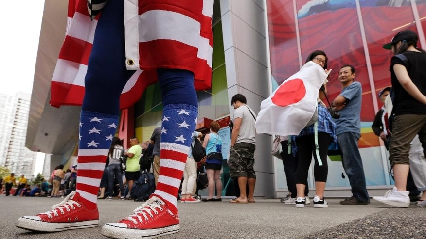 A fan of Japan looks at a United States fan as they stand outside BC Place stadium before the FIFA Women's World Cup soccer championship between the U.S. and Japan in Vancouver, British Columbia, Canada, Sunday, July 5, 2015. (AP Photo/Elaine Thompson)