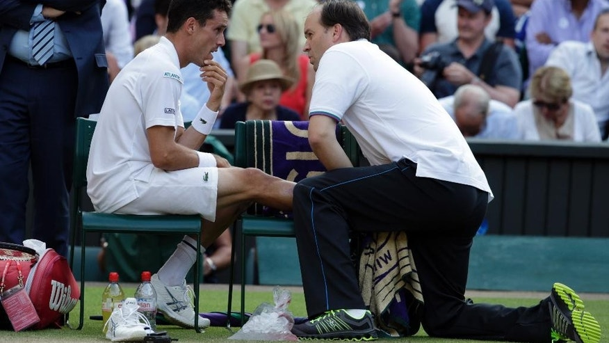 Roberto Bautista Agut of Spain receives treatment during the singles match against Roger Federer of Switzerland, at the All England Lawn Tennis Championships in Wimbledon, London, Monday July 6, 2015. (AP Photo/Alastair Grant)