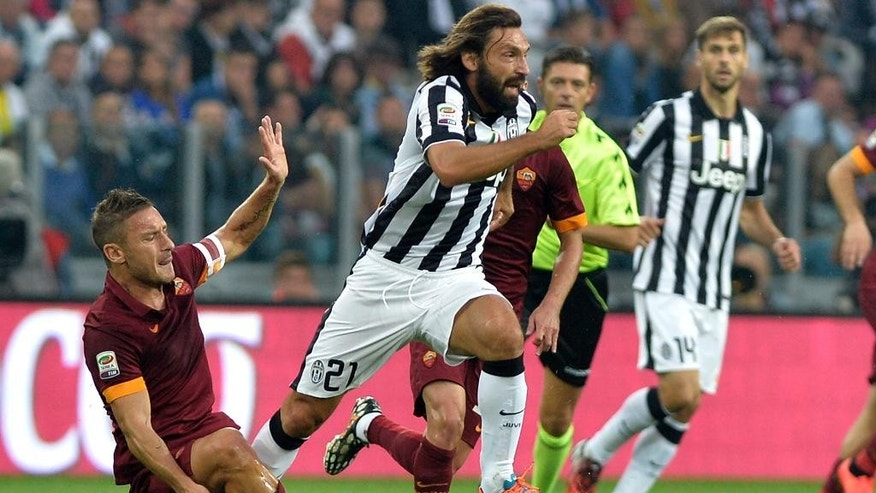 FILE - This is a Sunday, Oct. 5, 2014  file photo of Juventus' Andrea Pirlo  as her gets the ball past Roma' Francesco Totti during a Serie A soccer match at the Juventus stadium, in Turin, Italy. Italy playmaker Andrea Pirlo has joined Major League Soccer club New York City FC from Juventus. Juventus confirmed the news on its official Twitter account Monday July 6, 2015. (AP Photo/Massimo Pinca, File)