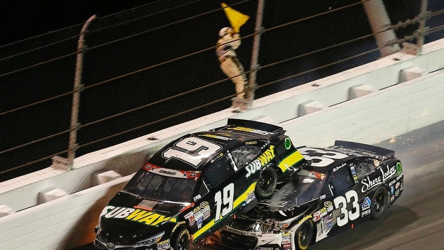 Brian Scott (33) goes under Carl Edwards (19) as they wreck in turn 2 during a NASCAR Sprint Cup series auto race at Daytona International Speedway, Monday, July 6, 2015, in Daytona Beach, Fla. (AP Photo/John Moore)