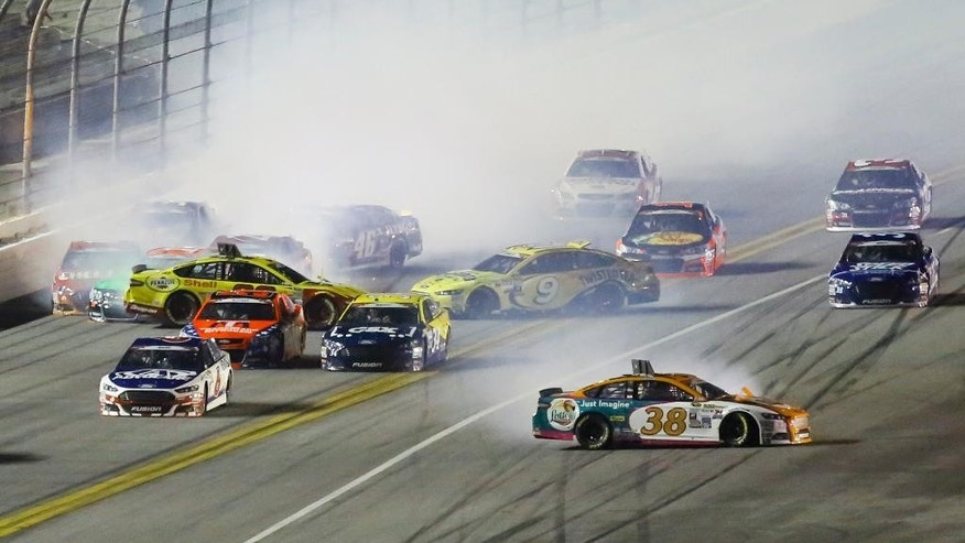 Mulitple cars, including David Gilliland (38), Sam Hornish Jr. (9) and Michael Annett (46) wreck coming out of turn 4 in a NASCAR Sprint Cup series auto race at Daytona International Speedway, Sunday, July 5, 2015, in Daytona Beach, Fla. (AP Photo/David Graham)