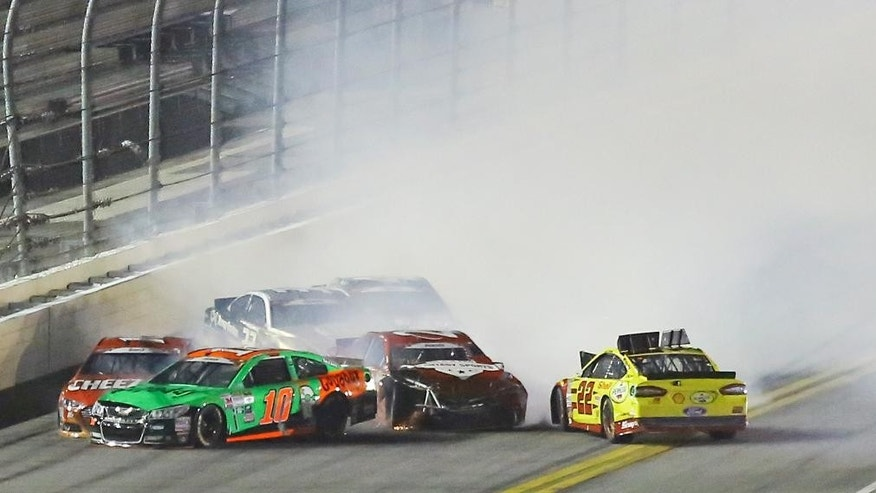 Danica Patrick (10), Jeb Burton, center, Joey Logano (22) are among a group of cars involved in a multi-car crash coming out of turn 4 during a NASCAR Sprint Cup series auto race at Daytona International Speedway, Sunday, July 5, 2015, in Daytona Beach, Fla. (AP Photo/David Graham)
