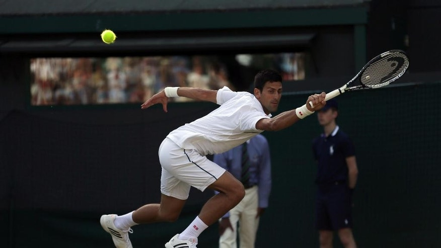 Novak Djokovic of Serbia makes a return to Kevin Anderson of South Africa during their singles match against at the All England Lawn Tennis Championships in Wimbledon, London, Monday July 6, 2015. (AP Photo/Tim Ireland)