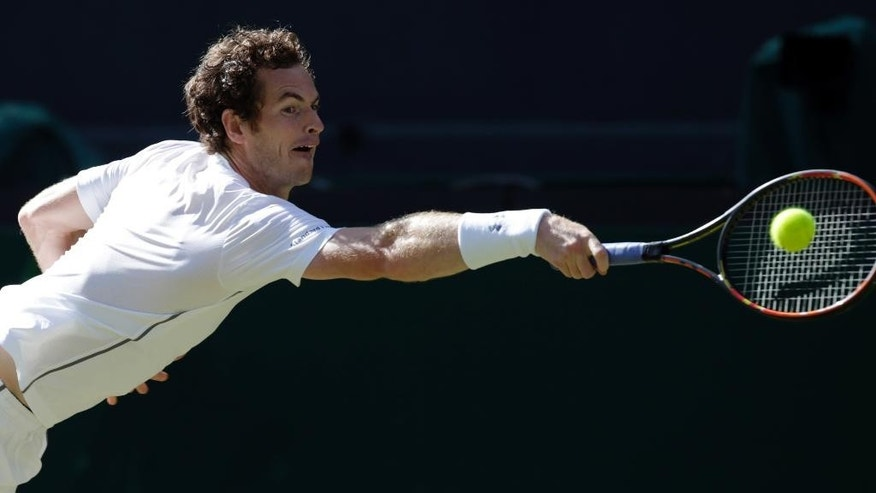 Andy Murray of Britain makes a return to Ivo Karlovic of Croatia, during their singles match at the All England Lawn Tennis Championships in Wimbledon, London, Monday July 6, 2015. (AP Photo/Alastair Grant)