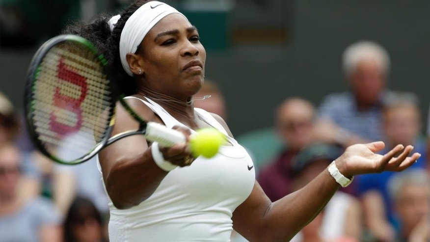 Serena Williams of the United States returns a ball to Venus Williams of the United States, during their singles match at the All England Lawn Tennis Championships in Wimbledon, London, Monday July 6, 2015. (AP Photo/Alastair Grant)