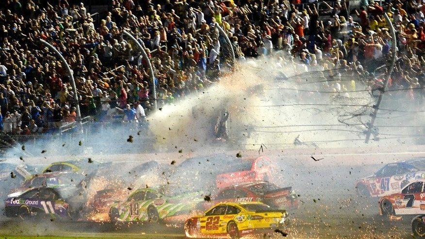 In thnis photo made early Monday, July 6, 2015, Austin Dillon (3) goes airborne and hits the catch fence as he was involved in a multi-car crash on the final lap of the NASCAR Sprint Cup series auto race at Daytona International Speedway in Daytona Beach, Fla. (AP Photo/Rob Sweeten)