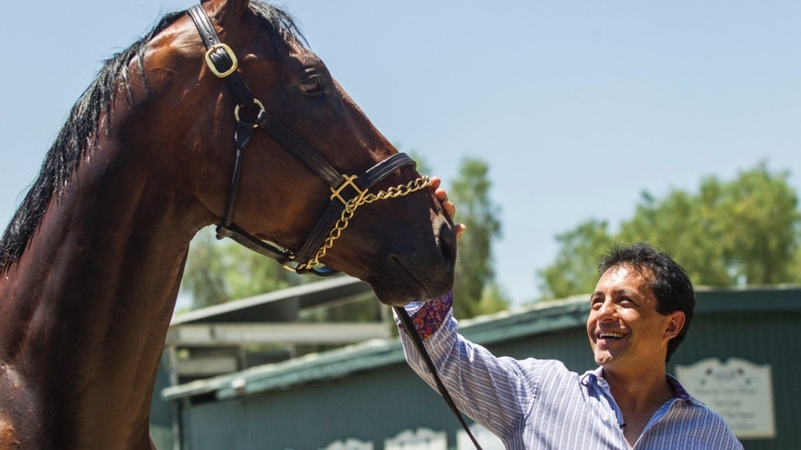 Victor Espinoza greets Triple Crown winner American Pharoah at Santa Anita Park in Arcadia, Calif., Thursday, June 18, 2015.