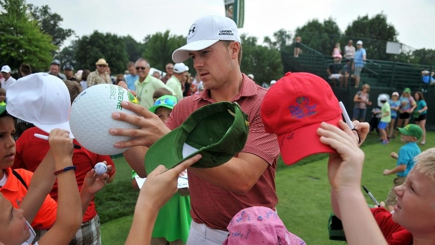 PGA golfer Jordan Spieth signs autographs at the John Deere Classic as he arrives to the practice range, Tuesday, July 7, 2015, in Silvis, Ill. (Paul Colletti/The Dispatch via AP)