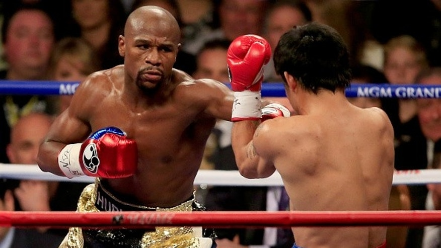 LAS VEGAS, NV - MAY 02:  Floyd Mayweather Jr. throws a left at Manny Pacquiao during their welterweight unification championship.
