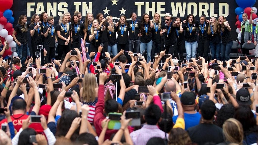 Members of the U.S. women's soccer team and fans celebrate the team's World Cup championship during a public celebration, Tuesday, July 7, 2015, in Los Angeles. This was the first U.S. stop for the team since beating Japan in the Women's World Cup final Sunday in Canada. (AP Photo/Jae C. Hong)
