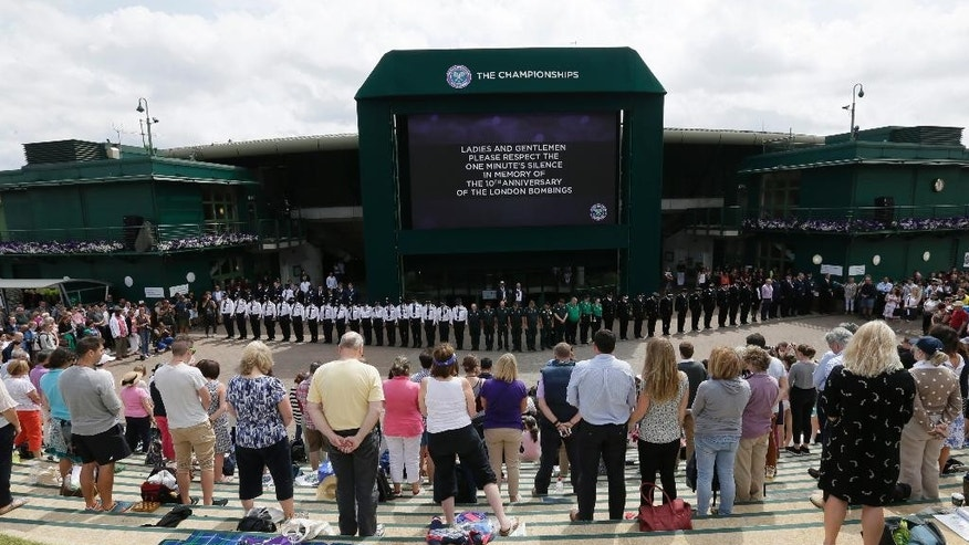 Spectators stand on Murray Mount to observe a minute's silence for the victims of the 7/7 bombings, on the tenth anniversary, at the All England Lawn Tennis Championships in Wimbledon, London, Tuesday July 7, 2015. (AP Photo/Tim Ireland)