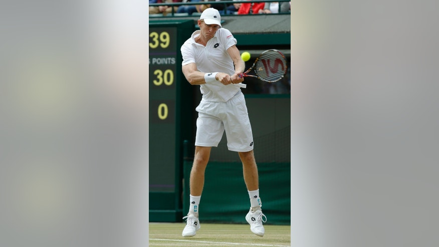 Kevin Anderson of South Africa returns a ball to Novak Djokovic of Serbia during their singles match against at the All England Lawn Tennis Championships in Wimbledon, London, Tuesday July 7, 2015. (AP Photo/Alastair Grant)