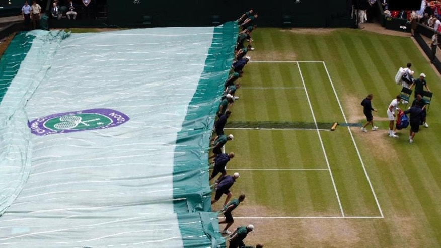 Ball boys cover Centre Court as rain starts to fall during the men's singles quarterfinal match between Andy Murray of Britain and Vasek Pospisil of Canada at the All England Lawn Tennis Championships in Wimbledon, London, Wednesday July 8, 2015. (AP Photo/Alastair Grant)