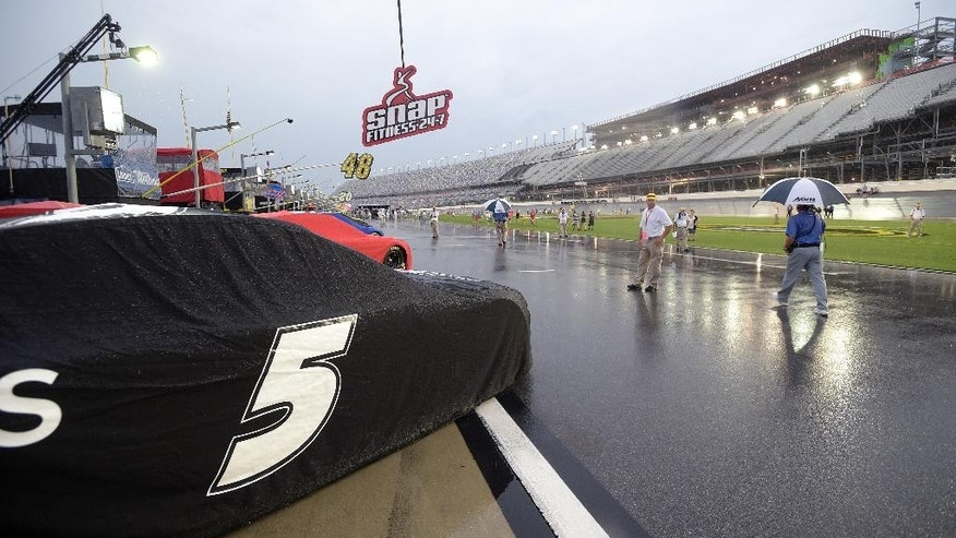 Race cars sit covered on pit road during a rain shower before a NASCAR Sprint Cup series auto race at Daytona International Speedway in Daytona Beach, Fla., Sunday, July 5, 2015. (AP Photo/Phelan M. Ebenhack)