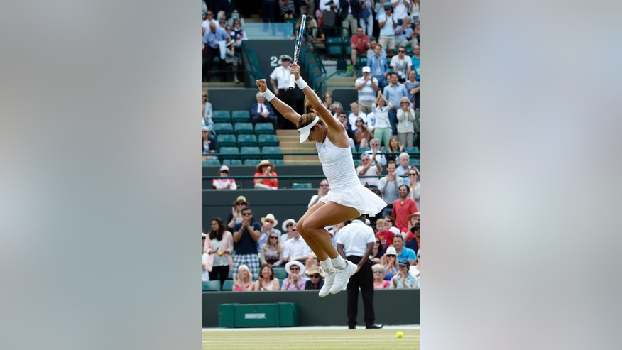 Garbine Muguruza of Spain celebrates winning the singles match against Timea Bacsinszky of Switzerland, at the All England Lawn Tennis Championships in Wimbledon, London, Tuesday July 7, 2015. Muguruza won 7-5, 6-3. (AP Photo/Alastair Grant)