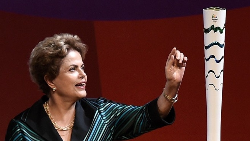 Brazilian President Dilma Roussef touches the Olympic torch during a ceremony on July 3, 2015 in Brasilia, Brazil.