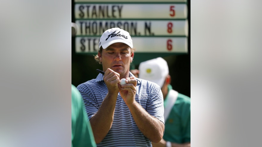 Nicholas Thompson signs a golf ball after finishing the first round of the John Deere Classic golf tournament tied for the lead with Justin Thomas, Thursday, July 9, 2015, in Silvis, Ill. (AP Photo/Charles Rex Arbogast)