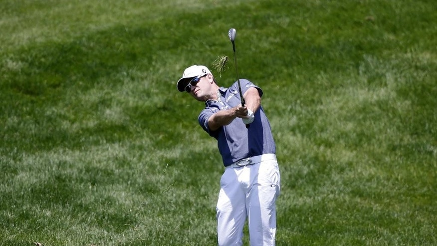 Zach Johnson watches his approach shot on the first hole during the first round of the John Deere Classic golf tournament Thursday, July 9, 2015, in Silvis , Ill. (AP Photo/Charles Rex Arbogast)